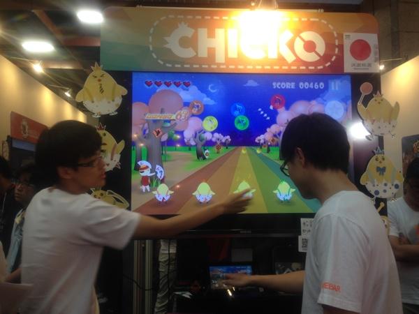 タッチパネルを使ったゲーム「CHICKO」の紹介をする学生
